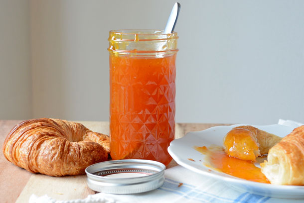 apricot jam on a croissant with a jar of preserves