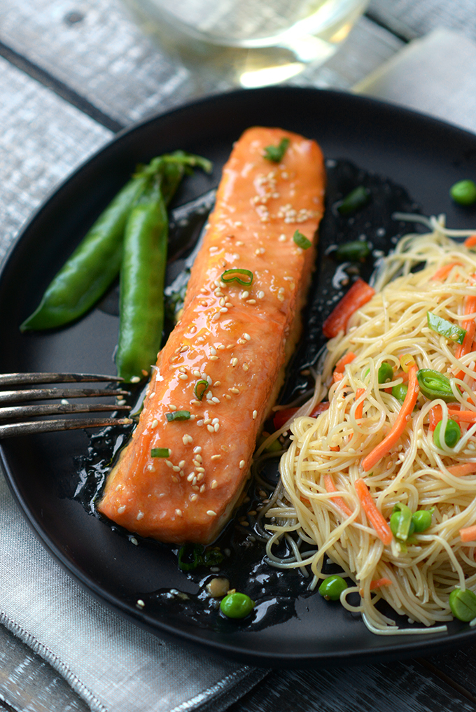Oven Baked Sesame Salmon on a black plate with sesame noodle salad and sugar snap peas