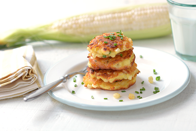 Corn fritters with chives stacked on a plate