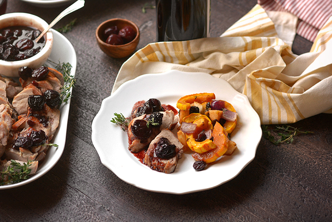 Pork tenderloin with cherry sauce and delicata squash on a plate