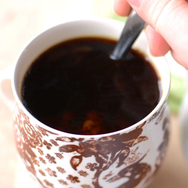 Stirring irish coffee creamer in a cup of coffee