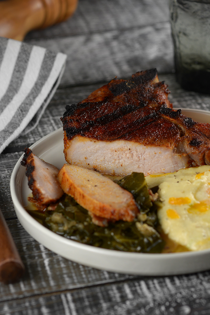 Sliced Grilled BBQ Dry Rubbed Pork Chops on a plate with collard greens and cheesy grits.